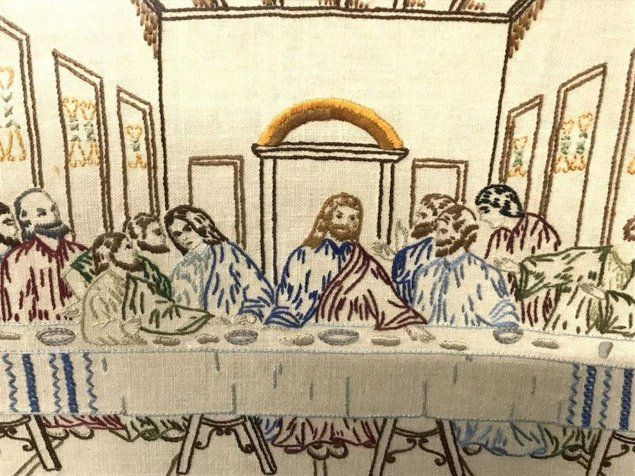 This unsigned pictorial sampler depicting the Last Supper, with Jesus and the apostles embroidered in multicolored  tones, measures 18 by 22¼ inches.
