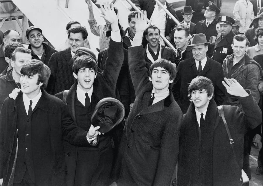 I Beatles salutano I fan al loro arrivo a New York, Kennedy Airport, 7 febbraio 1964. United Press International via Wikimedia Commons