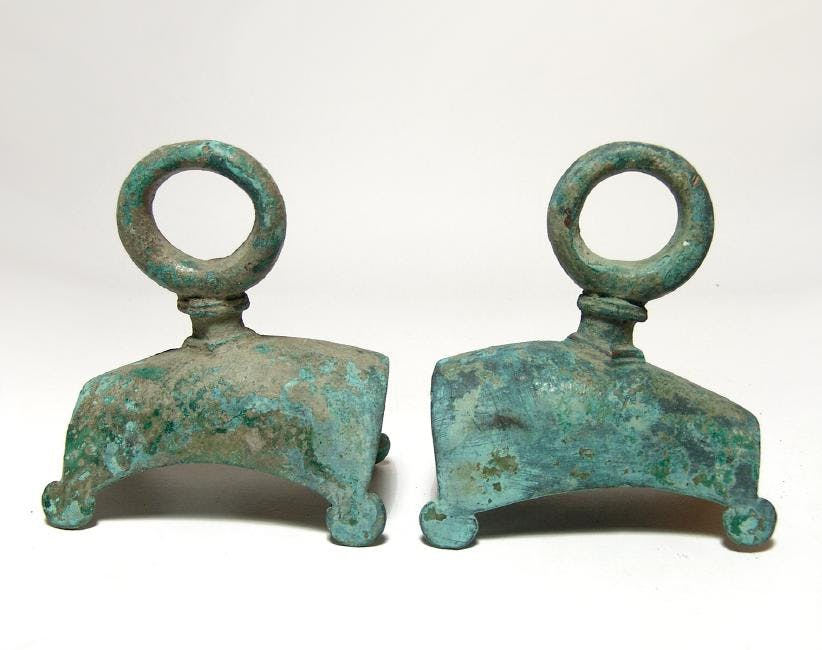 Pair of Roman bronze fittings (circa 1st-3rd century AD), from a chariot, a piece of furniture of solid construction, the body curved with circular extensions (est. $600-$800).