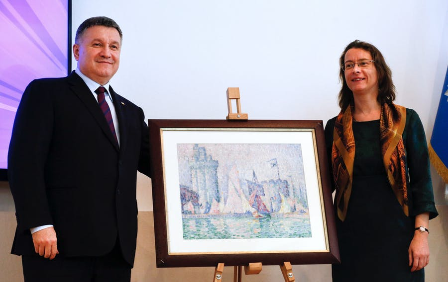 Ukrainian Interior Minister Arsen Avakov, left, and French Ambassador to Ukraine Isabelle Dumont pose for a photo with the 1915 painting. Image: Efrem Lukatsky via The Public's Radio