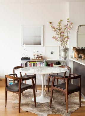 tulip-table-wood-chairs-hide-rug-white-walls-cat