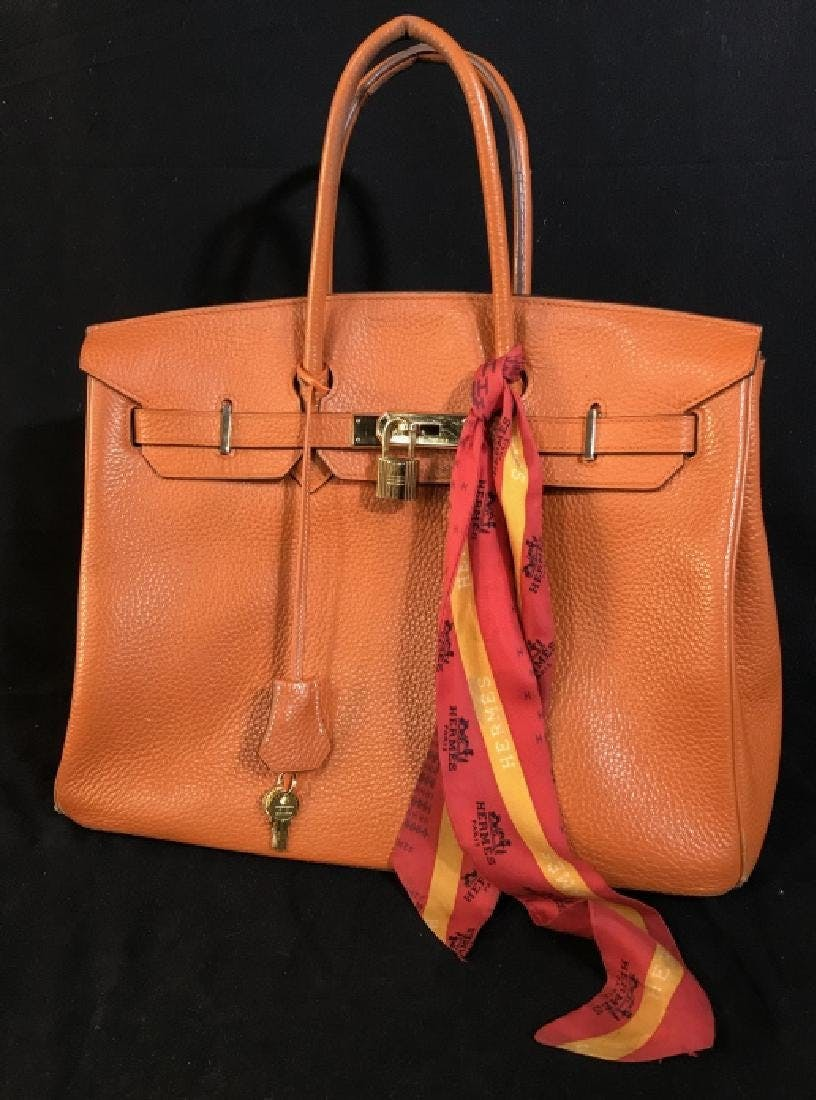 This Hermès Birkin bag ($500-1,500) in orange Togo and gold toned metal clasps, lock, and key, Consigner claims it is authentic, measures approx 13 inches wide to front seems x 16 inches to top of handles x 7 inches deep at base.
