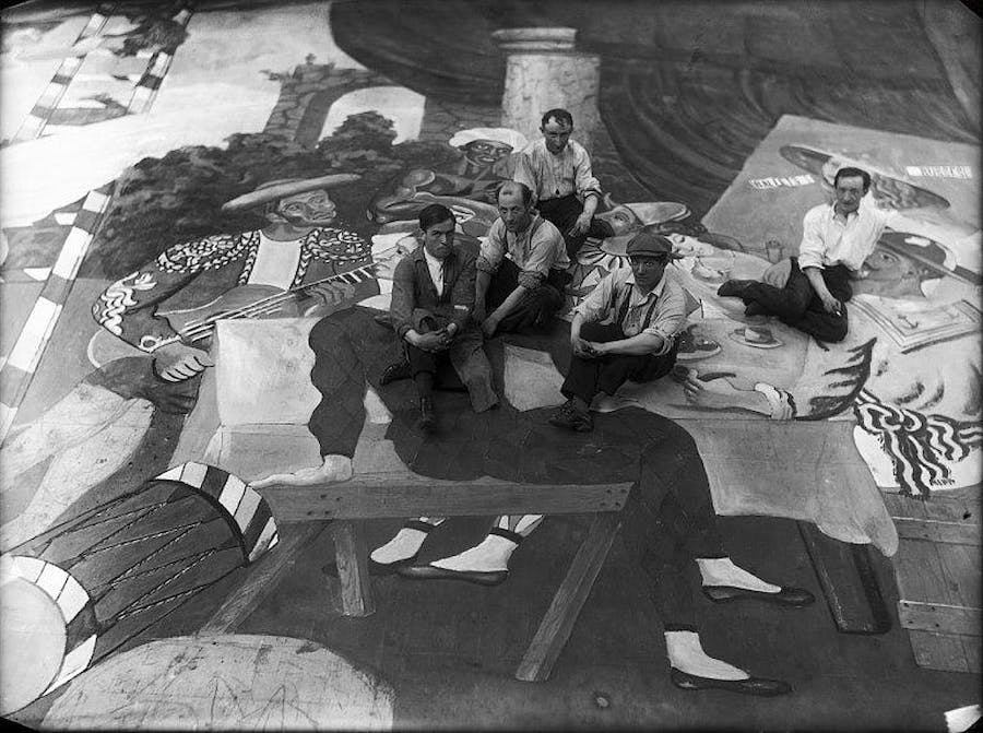 """Pablo Picasso (second from the right, wearing a cap), surrounded by stage workers during the preparations for the ballet """"Parade."""" Photo via Wikimedia Commons"""