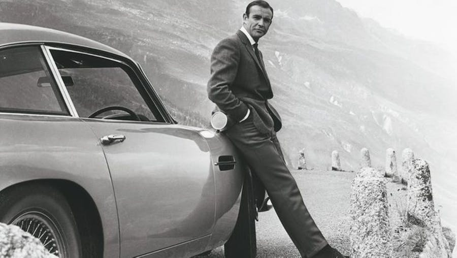 """Actor Sean Connery poses as James Bond next to his Aston Martin DB5 for movie 'Goldfinger"""", 1964 - Photo by Donaldson Collection - Michael Ochs Archives via Barneby.fr"""