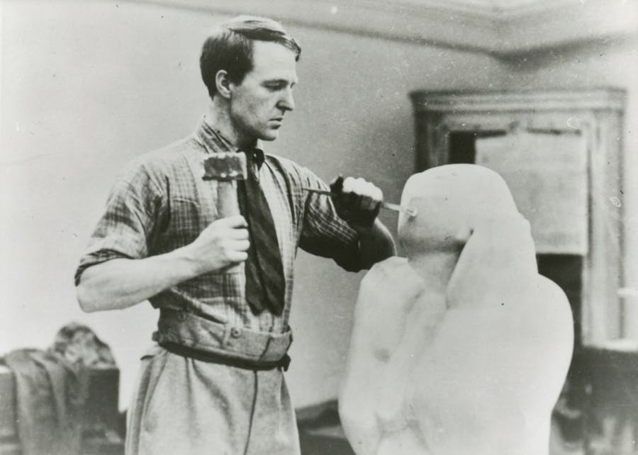 Photograph of Henry Moore carving at No.3 Grove Studios, Hammersmith, 1927 © The Henry Moore Foundation. All Rights Reserved Photo: Henry Moore Foundation Archive