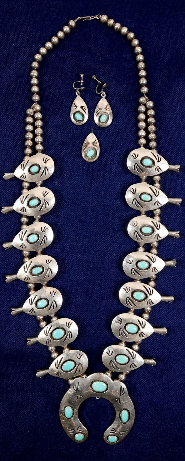 Native American jewelry consisting of a sterling silver squash blossom necklace, 18 inches long, a pair of earrings and a pendant to match. Made in New Mexico in the 1980s (est. $300-$500)