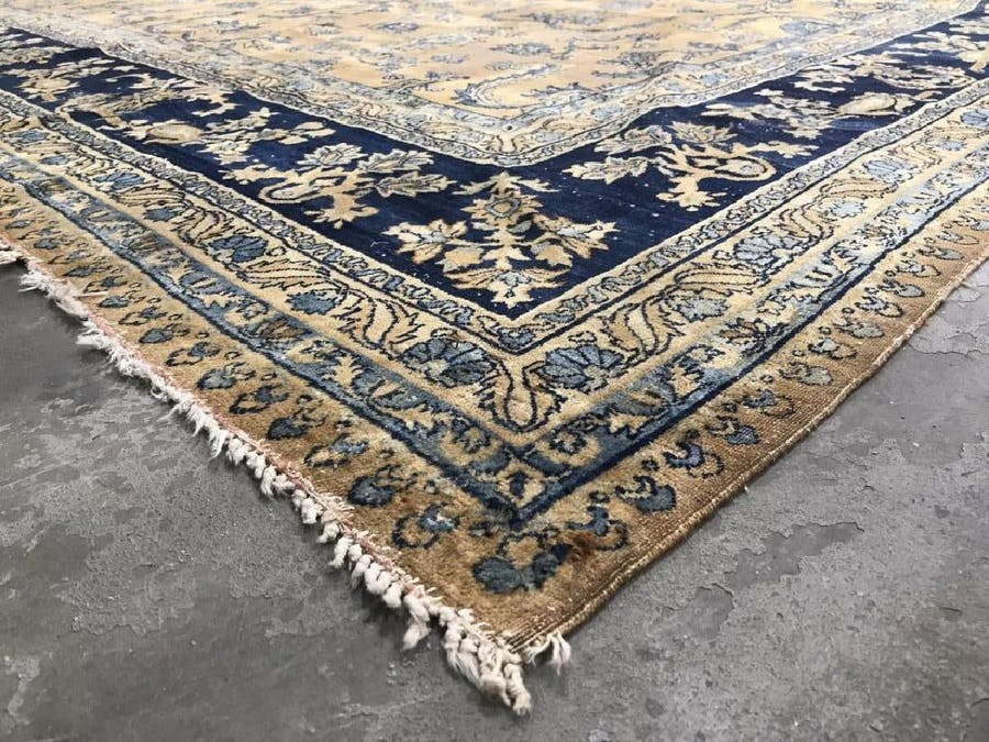 An antique handmade Kerman wool rug ($4/6,000) has a multi-toned floral, leaf and vine detail pattern in shades of light blue, beige and navy, 190 by 109 inches.